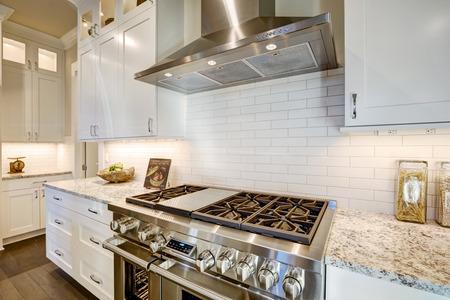 Mooie keuken is voorzien van een hoekje gevuld met roestvrijstalen fornuis, afzuigkap, witte ondergrondse tegel backsplash gecombineerd met granieten aanrecht. Northwest, VS. Stockfoto - 71729242
