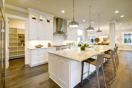 White kitchen design features large bar style kitchen island with granite countertop illuminated by modern pendant lights. Open door lead to walk-in pantry. Northwest, USA