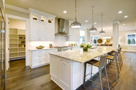Las características del diseño de la cocina blanca grande isla de cocina estilo de la barra con encimera de granito iluminado por las luces de techo modernas. plomo puerta abierta a la despensa. Noroeste, EE.UU.