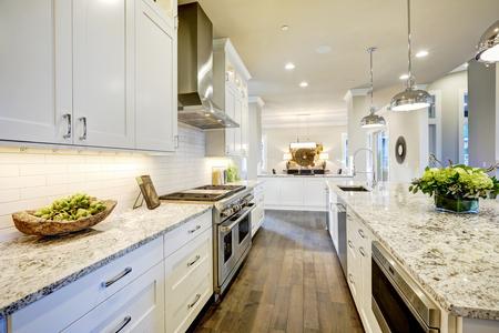 White kitchen design features large bar style kitchen island with granite countertop illuminated by modern pendant lights. Northwest, USA Foto de archivo