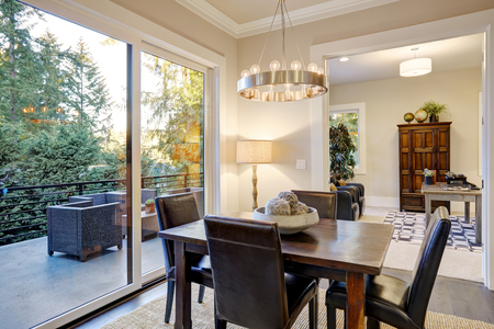 bellevue: Open dining space design with soft beige walls and rustic table with leather chairs next to exit to a beautiful deck. Norhtwest, USA