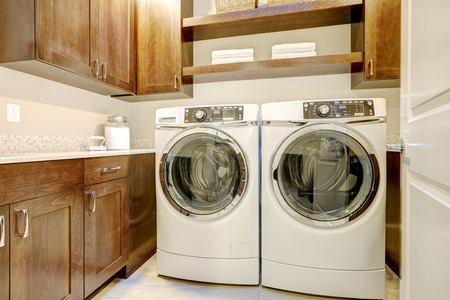 laundry room: White and brown laundry room features modern appliances placed under shelves and cabinets. Northwest, USA  Stock Photo