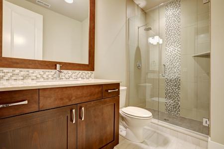 Glazen inloopdouche met witte metselwerk betegelde rand geaccentueerd met verticale mozaïektegels in een gloednieuwe badkamer. Northwest, VS.
