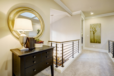 second floor: Second floor landing with black console table topped with a lamp placed under round gold mirror. Northwest, USA