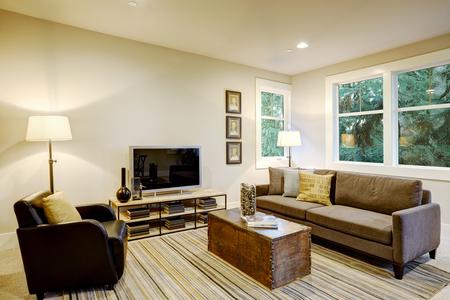 Interior de la habitación familiar con sofá gris frente a un sillón de cuero negro al otro lado de una mesa de café sobre una alfombra de rayas gris y marrón. Noroeste, EE. UU.