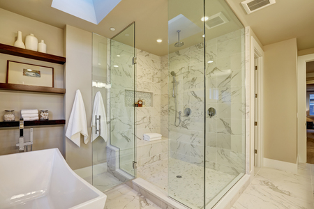 Amazing master bathroom with large glass marble walk-in shower, freestanding tub and skylights on the ceiling. Northwest, USA