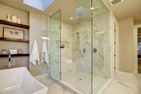 Verbazingwekkende master badkamer met grote glazen marmeren inloopdouche, vrijstaand bad en dakramen op het plafond. Northwest, USA Stockfoto - 70296414