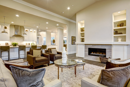 open topped: Chic living room design in natural colors and open plan. Furnished with glass top accent tables and beige sofas topped with brown pillows facing modern fireplace with built-in shelves. Northwest, USA  Stock Photo