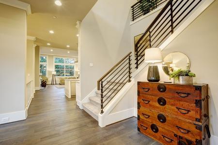 Light modern hallway design boasts vintage steamer trunk dresser next to staircase with metal horizontal railings. Northwest, USA
