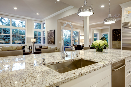 White kitchen design features large bar style kitchen island with granite countertop illuminated by modern pendant lights. Northwest, USA Foto de archivo