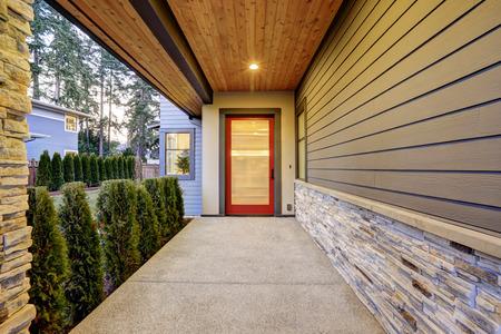Ingang van luxueuze nieuwbouw woning met lange overdekte veranda met plank plafond, natuurstenen muur ontwerp en moderne glanzende voordeur. Northwest, VS.