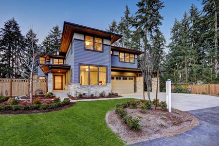 Luxe nieuwbouwhuis in Bellevue, WA. Moderne stijl huis beschikt over twee auto's garage omlijst door blauwe gevelbeplating en natuurstenen muur trim. Northwest, VS. Stockfoto - 70296417