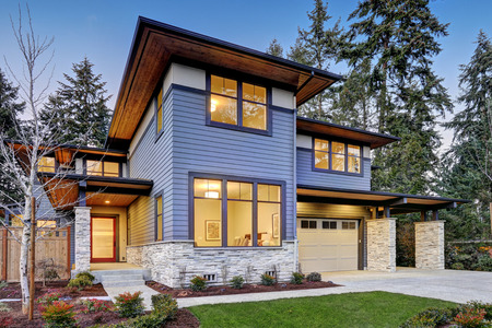 Luxurious new construction home in Bellevue, WA. Modern style home boasts two car garage framed by blue siding and natural stone wall trim. Northwest, USA