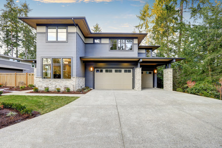 new construction: Luxurious new construction home in Bellevue, WA. Modern style home boasts two car garage framed by blue siding and natural stone wall trim. Northwest, USA