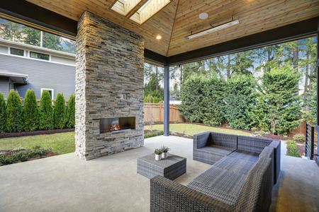 bellevue: Chic, elegant deck patio design features vaulted paneled ceiling with skylights over a floor to ceiling gray stone fireplace and large taupe wicker sofa with ottoman as coffee table. Northwest, USA