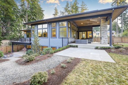 Luxury new construction home with blue siding and chic patio accented with stone fireplace. Northwest, USA