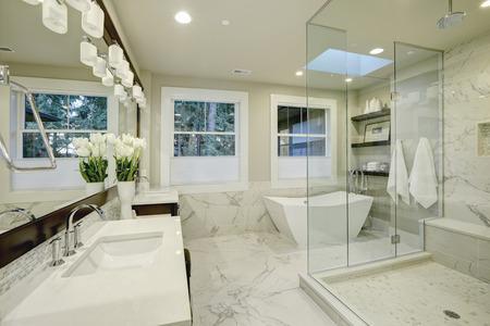 Increíble blanco y gris baño principal de mármol con cristal grande cabina de ducha, bañera independiente y claraboyas en el techo. Noroeste, EE.UU.