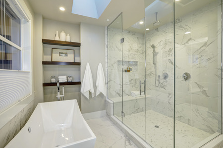 Amazing white and gray marble master bathroom with large glass walk-in shower, freestanding tub and skylights on the ceiling. Northwest, USA Archivio Fotografico