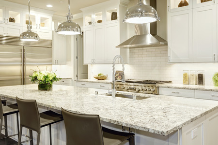 Las características del diseño de la cocina blanca grande isla de cocina estilo de la barra con encimera de granito iluminado por las luces de techo modernas. electrodomésticos de acero inoxidable enmarcados por los gabinetes de agitador blancos. Noroeste, EE.UU.