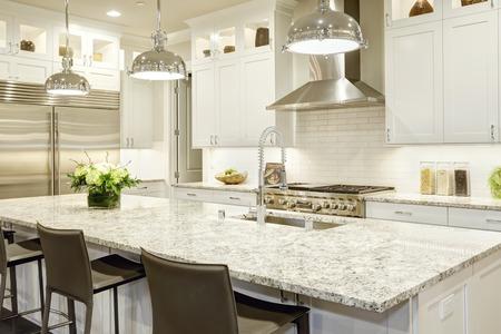 Weiße Küche Design verfügt über große Bar-Stil Kücheninsel mit Granit-Arbeitsplatte durch moderne Pendelleuchten beleuchtet. Edelstahl-Geräte von weißen Schüttler Schränke gerahmt. Northwest, USA Lizenzfreie Bilder