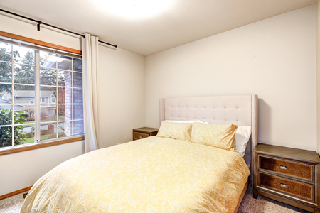 furnished: Beige bedroom interior features yellow bed with tufted headboard. Northwest, USA
