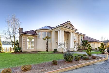 지중해 식 고급 워터 프론트 주택에는 낮은 기와 지붕, 치장 용 벽토 벽, 기둥이있는 베란다 및 아치 모티브가 있습니다. 잘 다듬어 진 조경 디자인은  스톡 콘텐츠