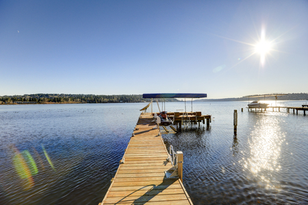 Private dock of waterfront home with jet ski lifts and covered boat lift, Picturesque view of Lake Washington on a bright sunny day. Northwest, USA
