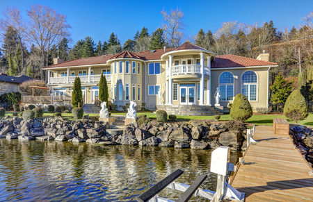 waterfront property: Private dock of luxurious waterfront home with jet ski lifts on a bright sunny day. Lake Washington. Northwest, USA