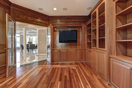 tv home: Wooden interior of empty room in luxury mediterranean home fitted with built in cabinets framed by paneled walls, also wall mounted flatscreen tv next to open glass double doors. Northwest, USA Stock Photo