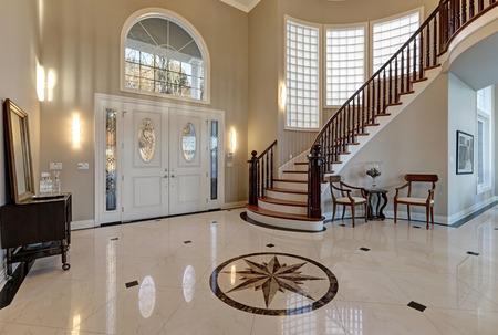 Impresionante vestíbulo de entrada de dos pisos con una gran cantidad de espacio cuenta con mármol suelo de baldosas de mosaico, puerta de entrada con ventana enmarcada arco y las luces laterales, gran escalera con barandilla de madera brillante curva. Noroeste, EE.UU.