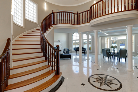 tiled floor: Stunning spacious two story entry foyer boasts marble mosaic tiled floor and grand staircase with glossy wood curved banister. The foyer flanked by formal dining room and living room. Northwest, USA Stock Photo