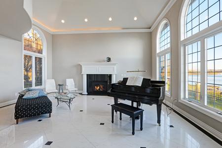 Luxe hoog plafond woonkamer is voorzien van beige ivoor muren framing grote gebogen ramen, traditionele open haard, zwarte vleugel naast de gezellige zithoek boven op glanzende marmeren vloer. Northwest, USA