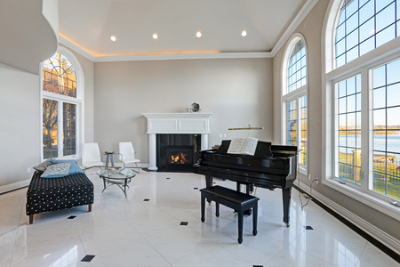 Luxury high ceiling living room features beige ivory walls framing large arched windows, traditional fireplace, black grand piano next to cozy sitting area atop glossy marble floor. Northwest, USA Standard-Bild