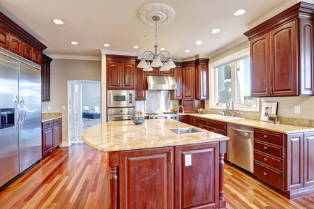 Warm and inviting kitchen with large kitchen island, cherrywood cabinets, sandy counter tops and modern stainless steel refrigerator. Northwest, USA Stock Photo