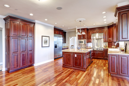 Warm and inviting kitchen boasts large kitchen island, cherrywood cabinets, sandy counter tops and modern stainless steel refrigerator. Northwest, USA