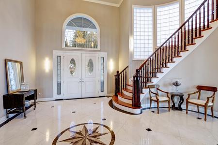 Prachtige twee verdiepingen ingangsportaal met veel ruimte voorzien van marmeren mozaïek tegelvloer, voordeur ingelijst met boogvenster en zijlichten, grote trap met glanzend hout gebogen banister. Noordwest, Verenigde Staten Stockfoto - 71023463