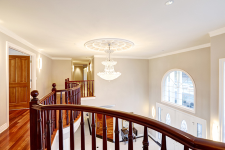 second floor: Second floor landing with glossy wood curved railings features crystal chandelier over spacious foyer  Northwest, USA