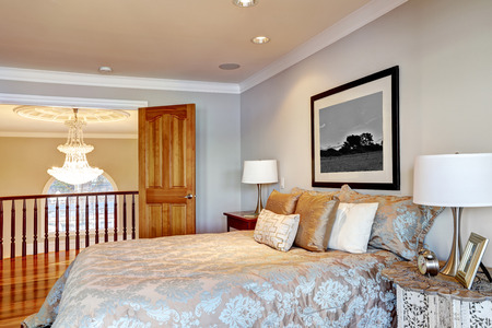 pale color: Chic master bedroom with pale grey walls paint color, queen bed dressed in blue and grey floral bedding and open doors to the landing with chandelier view. Northwest, USA Stock Photo
