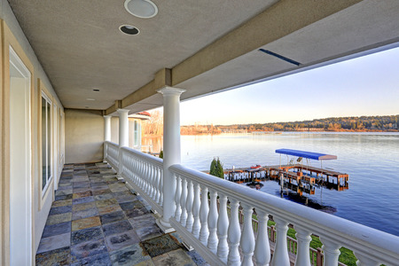 Balcony view with natural stone tile floor , white columns and railings, facing Lake Washington and private dock of luxurious Mediterranean style waterfront home. Northwest, USA Stock Photo