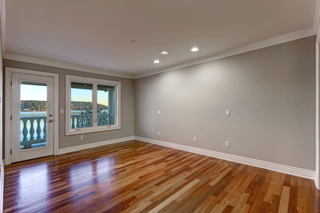 Empty room interior with soft grey walls paint color, glossy hardwood floor and door to balcony. Northwest, USA Stock Photo