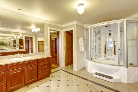 Luxurious master bathroom features Custom built shower with multi-functional jets, cherrywood vanity cabinet and glossy marble floor. Northwest, USA Stock Photo