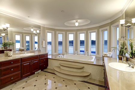 Luxurious master bathroom interior boasts jetted tub with curved windows facing the lake, two cherrywood vanity cabinets facing each other and glossy marble floor. Northwest, USA