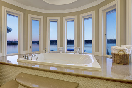 wooden floors: Luxurious master bathroom interior boasts jetted tub with curved windows facing the lake. Northwest, USA