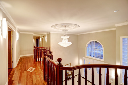 second floor: Second floor landing with glossy wood curved railings features crystal chandelier over spacious foyer.  Northwest, USA