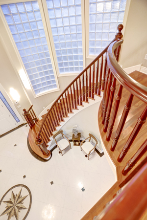 second floor: Panoramic view of spacious foyer from Second floor landing with glossy wood curved railings. Northwest, USA Stock Photo