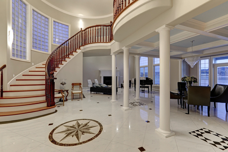 Stunning spacious entry foyer with columns boasts marble mosaic tile floor and grand staircase with glossy wood curved banister. The foyer flanked by formal dining room and living room. Northwest, USA
