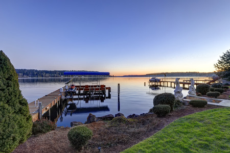 wa: Private dock of waterfront home with jet ski lifts and covered boat lift, Lake Washington. Northwest, USA Stock Photo