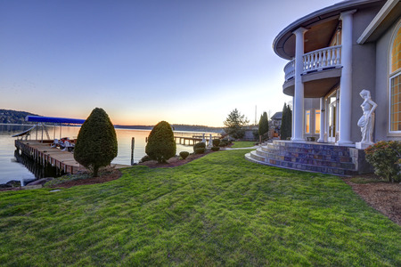 waterfront property: Luxurious Mediterranean style waterfront home exterior with view of the backyard area and private dock in Lake Washington during sunset time. Northwest, USA Stock Photo