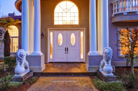 casa de estilo mediterráneo cuenta con lujo frente al mar elegante porche de techo alto con columnas blancas y estatuas de leones que conducen a la puerta de entrada con ventana de arco y las luces laterales, vista del atardecer. Noroeste, EE.UU.
