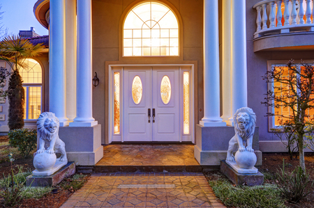 Mediterranean style luxury waterfront home boasts elegant high ceiling porch with white columns and lion statues leading to front door with arch window and sidelights, sunset view. Northwest, USA